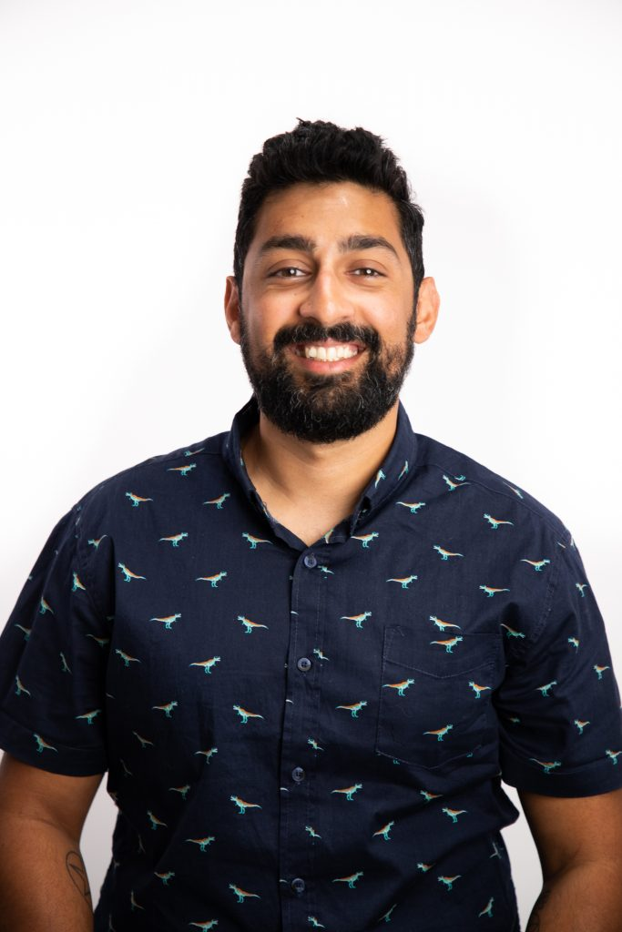 Image of Abhishek standing with a blue shirt on with a white background.