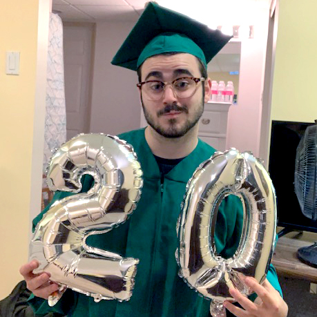 Man with brown hair and glasses in a green cap and gown