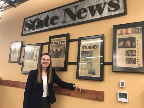 Woman with blonde/brown hair in front of framed news articles