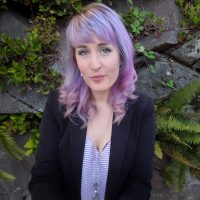 Woman with blue and purple hair earing a dark jacket and a purple and white striped shirt
